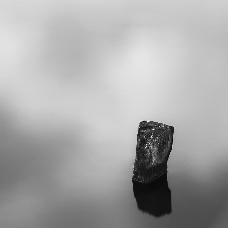 Dipping into my reflection - Minimalistic long exposure.  Part of an old pier structure rising from the water surface.